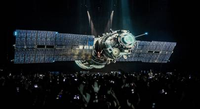 A hologram of a satellite floats above the crowd