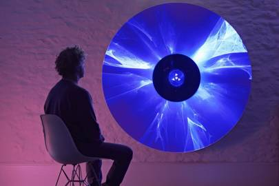Levine sitting with a parabolic dish that incorporates laser diodes and prisms