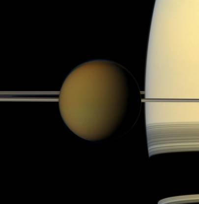 The colourful globe of Saturn's largest moon, Titan, passes in front of the planet and its rings