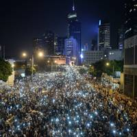 Pro-democracy demonstrators hold up their mobile phones during a protest near the Hong Kong government headquarters on September 29, 2014.  Over the course of the protest, thousands clashed with police and some were hospitalised as a result