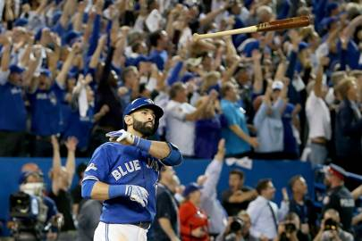 Jose Bautista of the Toronto Blue Jays throws his bat in the air after hitting a three-run homer in the seventh inning against the Texas Rangers