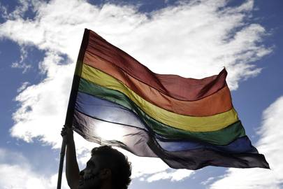 A man waves a rainbow flag during the Gay Pride Parade in Bogota, Colombia on 28 June, 2015