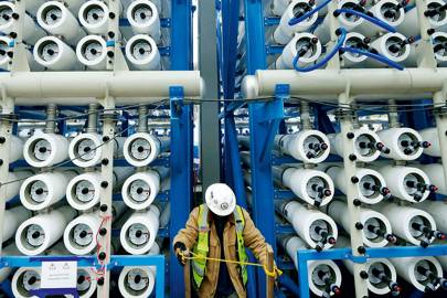 A worker checks the bank of pressure vessels that force seawater through the membranes