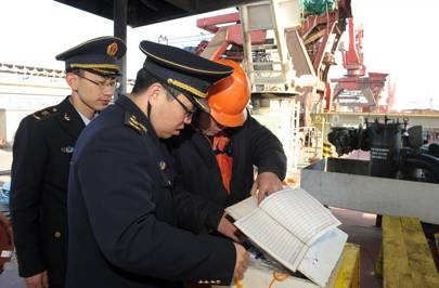Chinese officials inspect the cargo ship that collided with the sunk oil tanker Sanchi