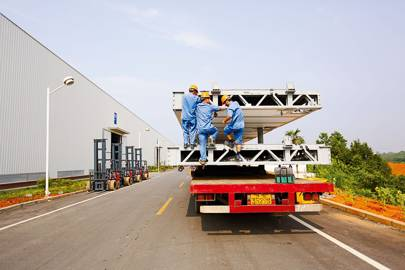 Workers load modules onto trucks at the building site