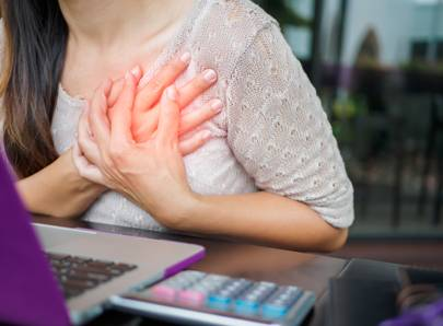woman clutching chest in depiction of a heart attack