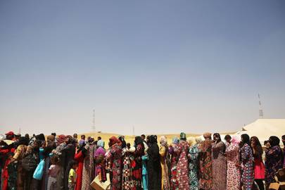 Iraqi women at the Khazair displacement camp wait for food and other items dispensed by the Iraqi Red Crescent in June 2014