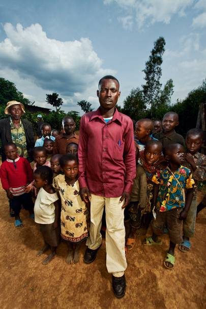 Gitambi's 26-year-old chief Jeandamascene Iyamuremye with some of the village's young population