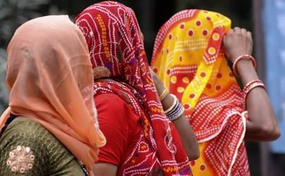 Indian women shield their faces from the sun during a heatwave