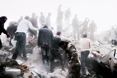 Local residents search for survivors after a regime air-strike in Aleppo