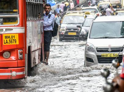 August 30 2017: people navigate their way through the waterlogged streets of Mumbai