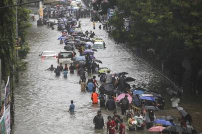 August 29 2017: People wade along a flooded street as cars become stuck during heavy rain in Mumbai