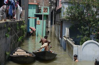 August 24 2017: Residents wade travel through flood waters in Malda in the Indian state of West Bengal
