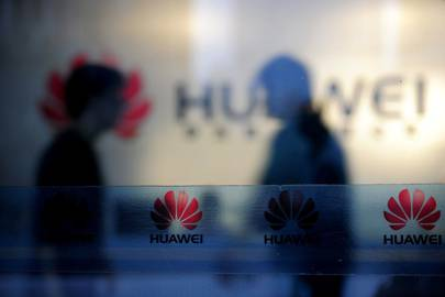 Staff and visitors walk pass the lobby at the Huawei office in Wuhan, China