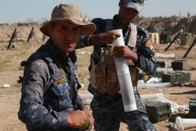 Two policemen ready their mortars to shell enemy positions, based on coordinates provided by artillery observers like al-Mayali