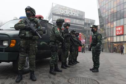 Armed police stand guard in the popular shopping and nightlife area of Sanlitun in Beijing on December 26, 2015.