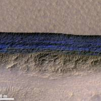 A cross-section of underground ice is exposed at the steep slope that appears bright blue in this enhanced-color view from the HiRISE camera on NASA's Mars Reconnaissance Orbiter