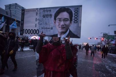 Protestors carry an image of Lee Jae-Yong at an ant-government march in South Korea