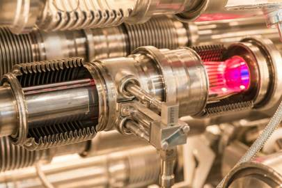 A pink glow illuminates the inside of this model of the LHC beam pipe, which is used to train engineers and technicians