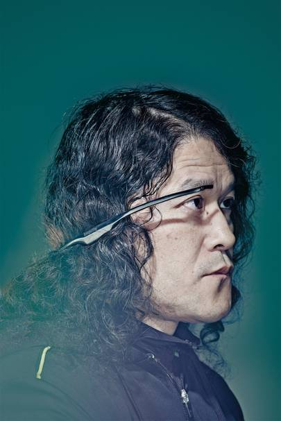Unlike the specs-style Google Glass, Telepathy One, worn here by inventor Takahito Iguchi, is secured by earbuds