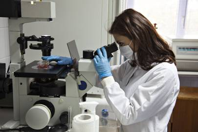Woman studying samples on a microscope in a lab