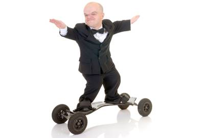 """Little businessman, dwarf in a formal suit with bow tie surfing on skateboard"""