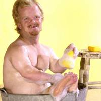 """Tiny man takes a bath in a bucket of soapy water with a rubber ducky"""