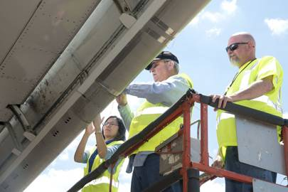 Nasa materials scientist Mia Siochi and systems engineer Mike Alexander, from the Langley Research Centre in Hampton, Virginia, and Boeing technician Felix Boyett count insect residue on the right wing of Boeing's ecoDemonstrator 757 aircraft.
