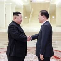 North Korean leader Kim Jong-Un (L) shakes hands with South Korean chief delegator Chung Eui-yong (R) during negotiations