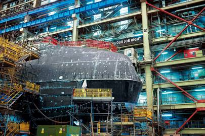 "An Astute-class submarine in Devonshire Dock Hall in Cumbria. The sub has a 2076 sonar suite as powerful as 2,000 laptops. The sign says: ""Lives Depend on Us Doing Our Job Right"""