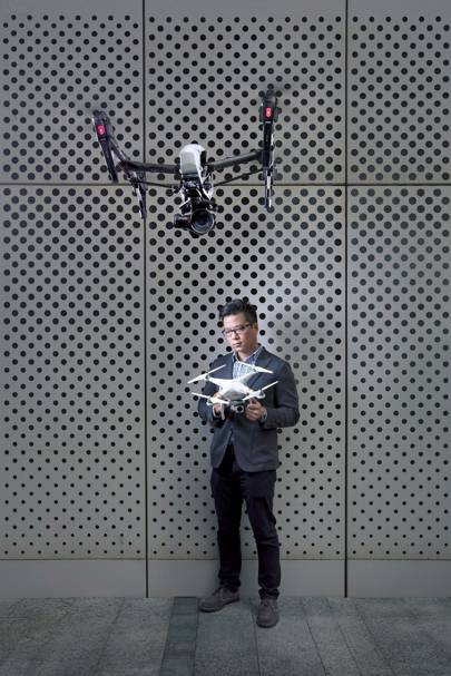 DJI product manager Paul Pan holds a Phantom 3 Professional drone