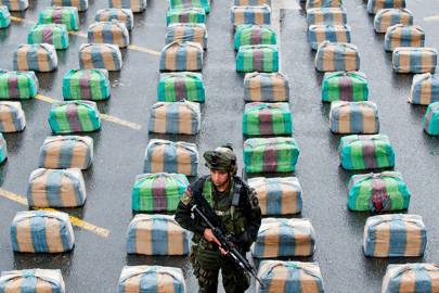 A member of an anti-drug police unit stands guard over marijuana packages seized from FARC guerrillas in Colombia