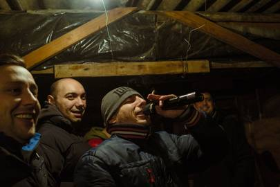 Men gather in a garden shed for moonshine and winter caroling. Holding the mic is a resident who profited from political websites