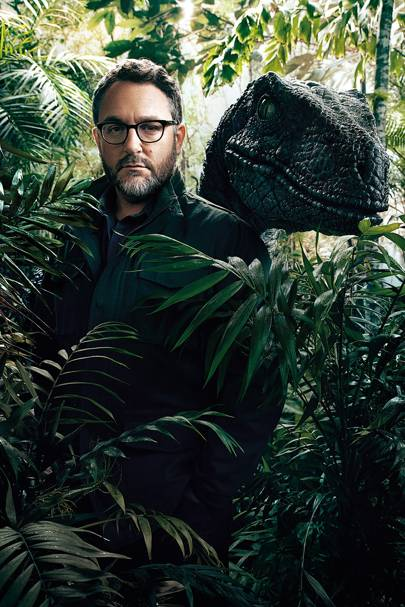 "Colin Trevorrow with a prosthetic ""Jurassic World"" velociraptor"