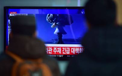 People watch a news report on North Korea's first hydrogen bomb test at a railroad station in Seoul on January 6, 2016. The image on the screen is from nuclear tests carried out by other countries