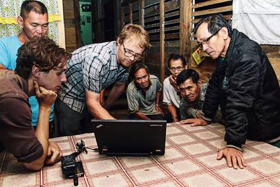 Nick Kelasau (left, standing), Helan and Jacobsen study satellite images of Samling operations with Penan residents of Long Lamai