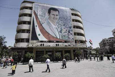 Syrians walk past a giant campaign poster for Syrian president Bashar al-Assad on 1 June 2014. The Syrian Electronic Army, which has operated since 2011, has been targeted scores of western news organisations and technology companies in support of Assad