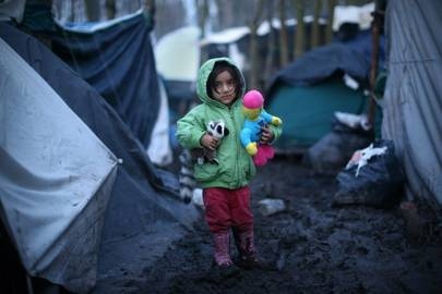 A Kurdish girl holds her toys as she stands in the mud at a migrant camp in Dunkirk, France