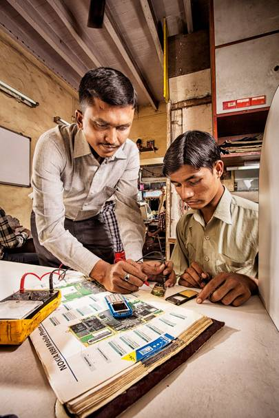 At the back of his Mumbai shop, Satish Rai teaches a student the fundamentals of frugality