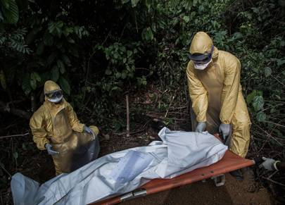 Healthcare workers in protective equipment bury a 13-year-old boy who died of Lassa fever on March 5, 2014 in Bo district, Sierra Leone
