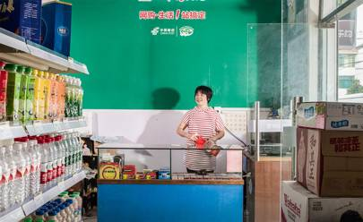 Qiu Sai Zhen behind the counter of her Ule store in Zan Gong village