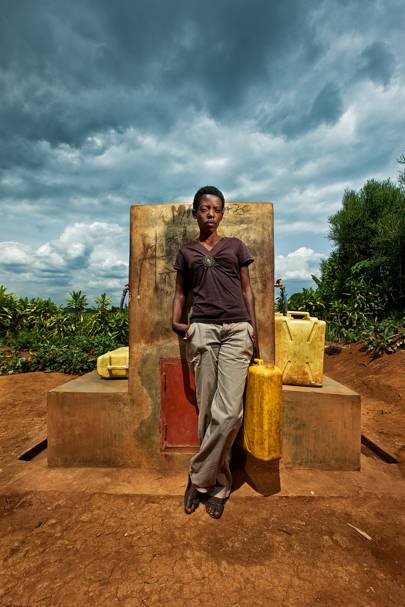 Redempta Mutezinka runs Gitambi's running-water kiosk.  She charges ten Rwandan francs (1p) for a 20-litre jerry can