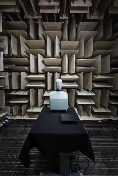 A head-and-torso simulator sits next to an Xbox One X prototype inside one of Microsoft's anechoic chambers