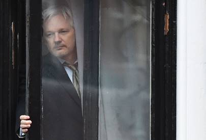 Julian Assange peers through the window of the Ecuadorian embassy