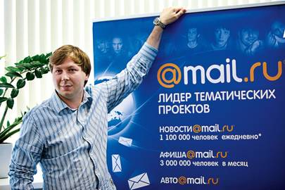"Dimitry Grishin pictured in 2009. The figures behind him list the ""topical categories"" that Mail.Ru was then a leader in"
